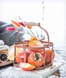 Still life fresh persimmon. In a basket on a serving table preparation for breakfast concept of holding Stock Image