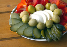 Still life with fresh and pickled vegetables on the plate on a wooden surface Royalty Free Stock Photos