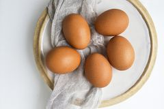 Still life with fresh raw eggs on plate on white background. Copy space. royalty free stock photography