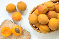 Still life with fresh ripe apricots. Apricots in a wicker wooden plate, on a wooden board. Still life with fresh ripe apricots. Apricots in a wicker wooden plate Royalty Free Stock Photography