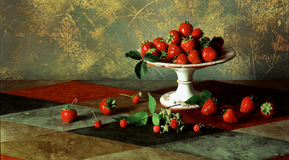 Still life with fresh ripe red berries and ceramic pedestal plat. E for fruit on abstract mottled background Stock Photo