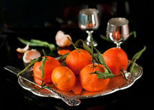 Still life of fresh tangerines with leaves on a tray Stock Photos