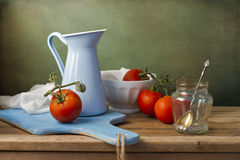 Still life with fresh tomatoes and tableware. On wooden table Stock Photos