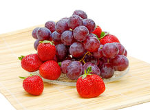 Still life of fruit. fresh grapes and strawberries. On a white background Stock Photo