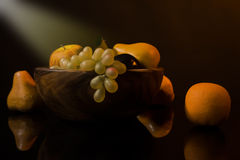 Still-life with fruit in a wooden dish. Picture of a still-life with fruit in a wooden dish royalty free stock photos