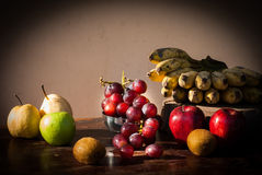 Still life Fruits with Chinese pear,kiwi,Red apple,grapes and Cu. Ltivated Banana on the wooden table Stock Photo