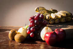 Still life Fruits with Chinese pear,kiwi,Red apple,grapes and Cu. Ltivated Banana on the wooden table Stock Photos