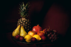 Still life of fruits. A still life with colorful fruits over a dark red background Stock Images