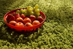 Fruits green grapes, peach or nectarines, strawberries in retro basket on green floor background. stock image