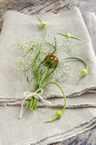 Still life with garlic buds and bouquet flowers on linen tablecloths Stock Image
