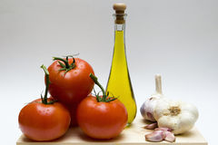 Still life with garlic, oil and tomatoes. Four branch tomatoes and a bottle of olive oil and two heads of garlic Stock Image
