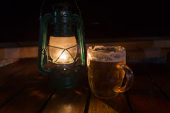 Still life with gas lamp and glass of beer. Burning gas lamp and  mug of lager beer stand on  wooden table at night Royalty Free Stock Image