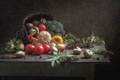 Still Life Gifts of Autumn. Cornucopia, healthy food, with a large wicker basket, from which poured vegetables, fruits and mushrooms mushrooms, pumpkins royalty free stock photos