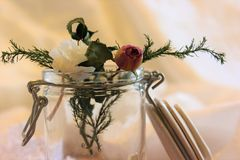 Still life. Glass jar with dried flowers on a wooden table and a white background Stock Photography