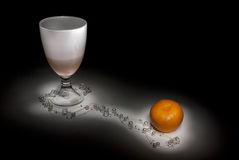 Still-life glass and tangerine Stock Image