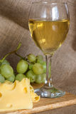 Still life with glass of white wine, cheese and grapes Royalty Free Stock Photos