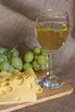 Still life with glass of white wine, cheese and grapes Stock Image