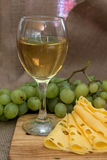 Still life with glass of white wine, cheese and grapes Stock Photography