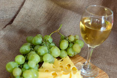 Still life with glass of white wine, cheese and grapes Stock Images