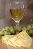 Still life with glass of white wine, cheese and grapes Stock Photo