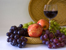 Still Life with a glass of wine. Composition of fruits (apples, green and blue grapes) and a glass of red wine on a basket Royalty Free Stock Photos