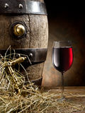 Still-life with glass of wine and barrel. Still-life with glass of wine and barrel on the table in the cellar Stock Photography