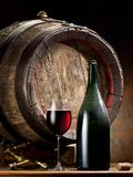 Still-life with glass of wine, bottle and barrel. Royalty Free Stock Photography