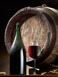 Still-life with glass of wine, bottle and barrel. Royalty Free Stock Images