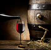 Still-life with glass of wine, bottle and barrel. Stock Image