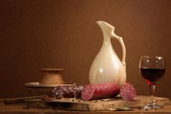 Still-life with a glass of wine and sausage Stock Image