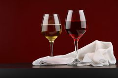 Still life with glasses of red and white wine. On Burgundy background royalty free stock photo