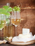 Glasses of white wine, bottle and cheese Stock Photography