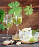 Glasses of white wine, bottle and cheese Stock Image