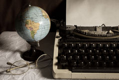 Still life globe and eyeglasses with typewriter. Royalty Free Stock Photo