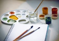 Still life with gouache paints, a palette, a notebook, brushes and a glass of water royalty free stock image