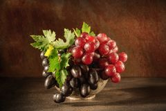 Still life with grape in the antique copper tin cup.  Royalty Free Stock Images