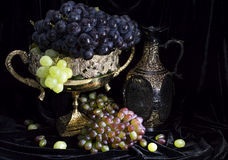 Still life with grape in vase and wine bottle. Vintage still life with the decorated vase full of ripe blue and green grape and with wine bottle on velvet Royalty Free Stock Photography
