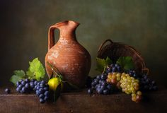 Still life with grapes. In the basket and jug Stock Image