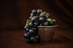Still life grapes in cup on brown fabric background. Grapes in cup on brown fabric background Royalty Free Stock Images