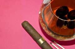 Still Life - grapes in a glass of cognac, cigars a Stock Photos