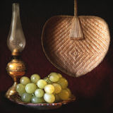 Still life, grapes, oil lamp and fan Royalty Free Stock Photos