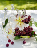 Still life with grapes and orchids in the garden. Still life with grapes and orchids on table with carafe and wine glasses in backyard Royalty Free Stock Images