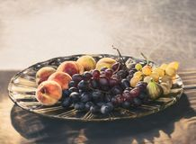 Still life with grapes and peaches. On a glass plate Royalty Free Stock Photography