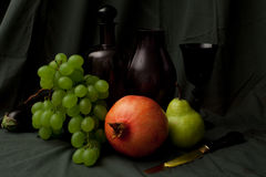 Still life with grapes, pomegranate, vine and gold knife. Sophisticated flemish still life with pear, grapes, pomegranate, cherrys, decanter and gold knife Stock Photos