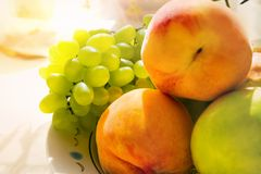 Still life of grapes of two peaches and an apple close-up in soft focus royalty free stock photo