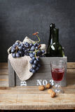 Still life with grapes,walnuts,empty wine bottle and a glass of wine Stock Photos