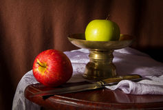 Still life green and red apples with metal dish and knife. Royalty Free Stock Images