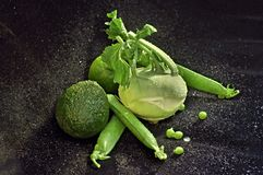 Still -life with green vegetables on black velvet with water drops Royalty Free Stock Images