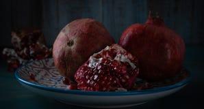 Still life grenade fruit. Feed on a black background.