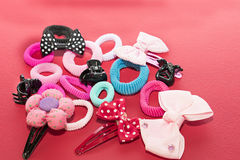Still life with hair accessories. Still life with buckles of flower shapes and bows, elastic bands and hair clips. Red background stock photography